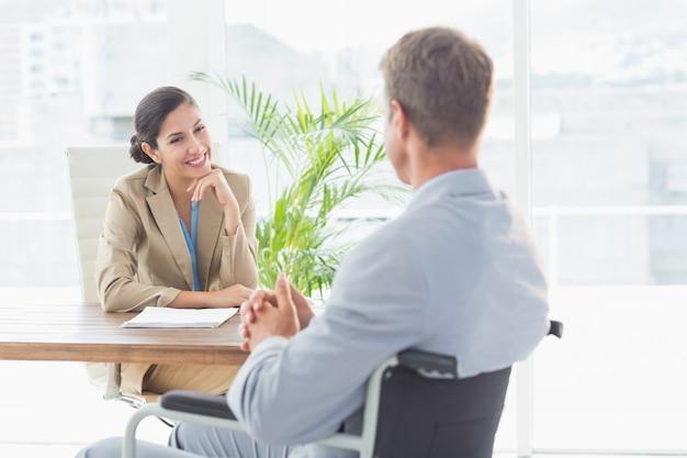 Femme d'affaires souriant interviewer un candidat handicapé