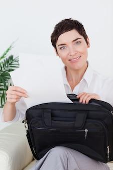 Femme d'affaires souriant, mettre des papiers dans son sac
