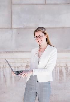 Femme d'affaires souriant avec ordinateur portable dans la rue