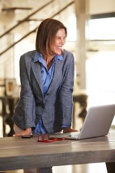 Femme d'affaires souriant avec ordinateur portable