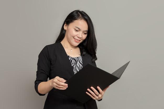 Femme d'affaires souriant tout en regardant et en tenant le dossier