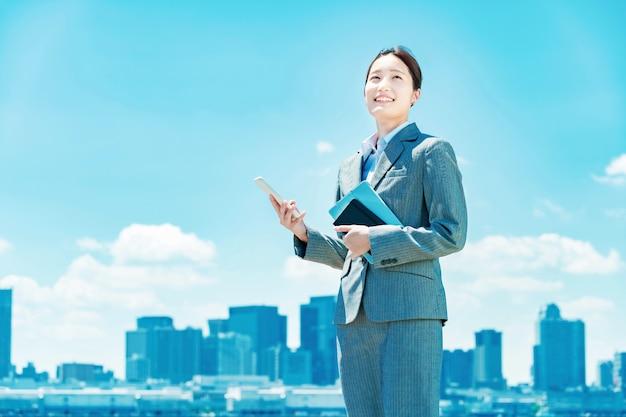 Femme d'affaires souriante asiatique tenant un smartphone
