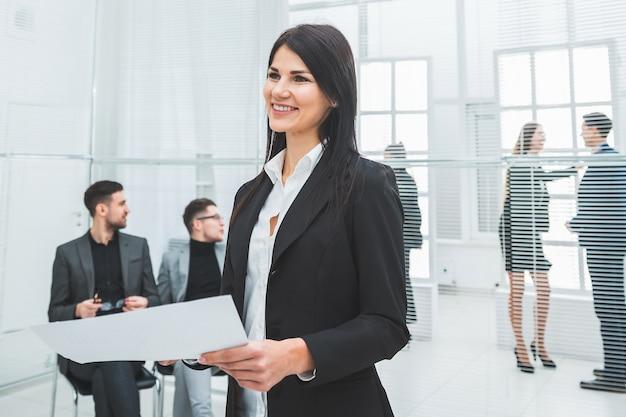 Femme d'affaires souriante avec un document debout au bureau. photo avec copie-espace