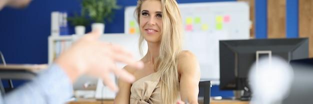 Femme d'affaires souriante est assise à table et communique avec un collègue.