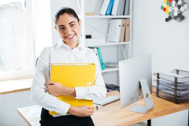 Femme d'affaires souriante et heureuse assise sur la table avec des documents au bureau et regardant à l'avant