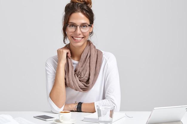 Femme d'affaires souriante à lunettes rondes