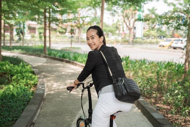 Femme d'affaires souriante, monté sur son vélo pliant