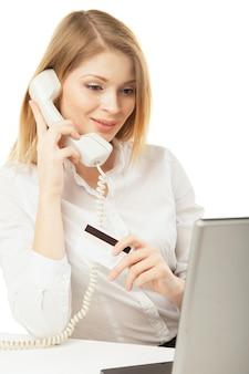 Femme d'affaires souriante avec ordinateur portable, carte de crédit et téléphone sur fond blanc