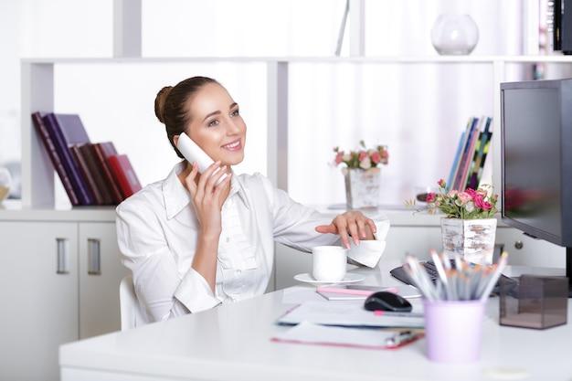 Femme d'affaires souriante parlant au téléphone au bureau.