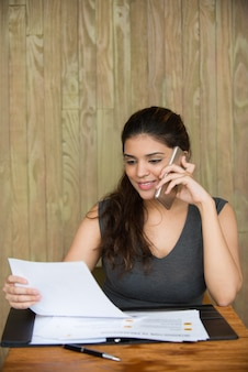 Femme d'affaires souriante parlant au téléphone et travaillant