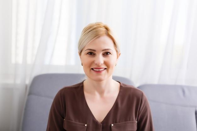 Une femme d'affaires souriante parle avec un client distant regardant la caméra appelant à un entretien d'embauche en ligne, un webinaire de formation en ligne, une formation vidéo de tournage d'une enseignante, une vue webcam