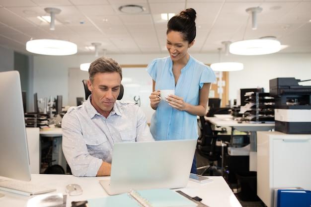 Femme d'affaires souriante, parler avec un collègue masculin au bureau