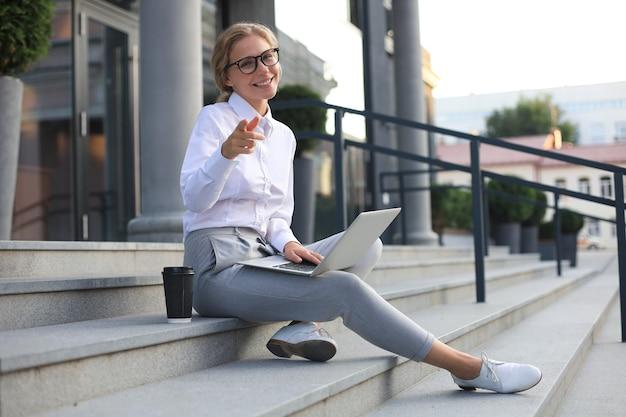 Femme d'affaires souriante pointant son doigt vers vous.