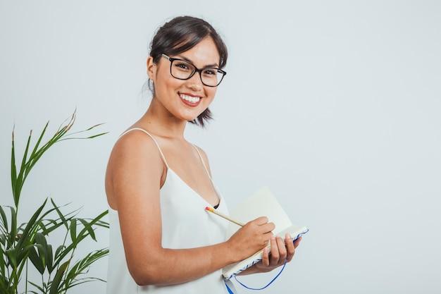 Femme d'affaires souriante posant et écrit sur son journal