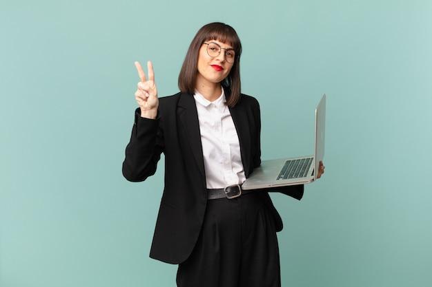 Femme d'affaires souriante et semblant amicale, montrant le numéro deux ou la seconde avec la main vers l'avant, compte à rebours