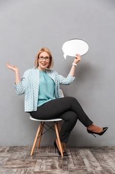 Femme d'affaires souriante tenant la bulle de dialogue.