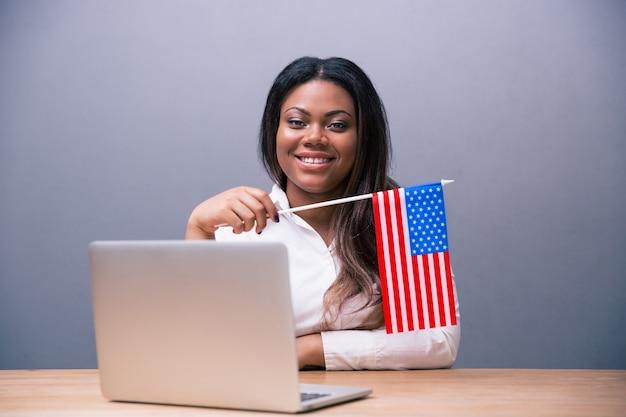 Femme d'affaires souriante tenant le drapeau américain