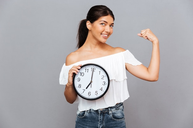 Femme d'affaires souriante tenant une horloge et montrant des biceps isolés sur un mur gris
