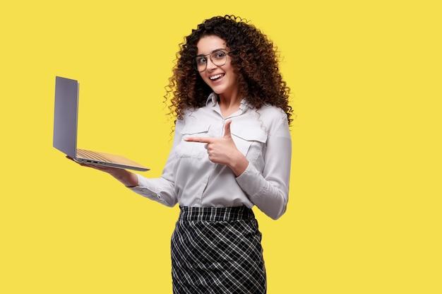 Femme d'affaires souriante tient un ordinateur portable et pointe son doigt dessus. une femme a gagné un casino en ligne. paris sportifs, gains, loterie