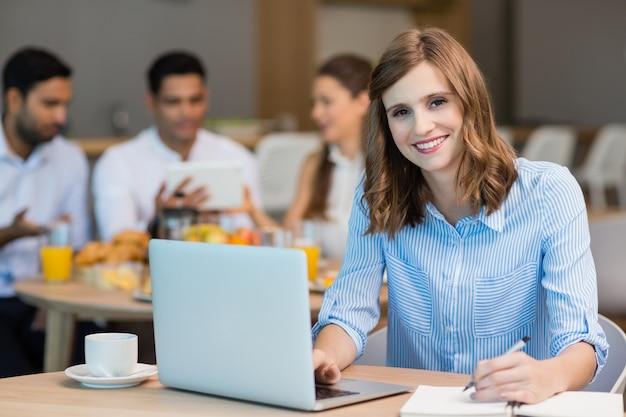 Femme d'affaires souriante travaillant sur un ordinateur portable tout en prenant un café au bureau