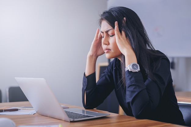 Femme d'affaires stressante au bureau fatiguée et ennuyée.