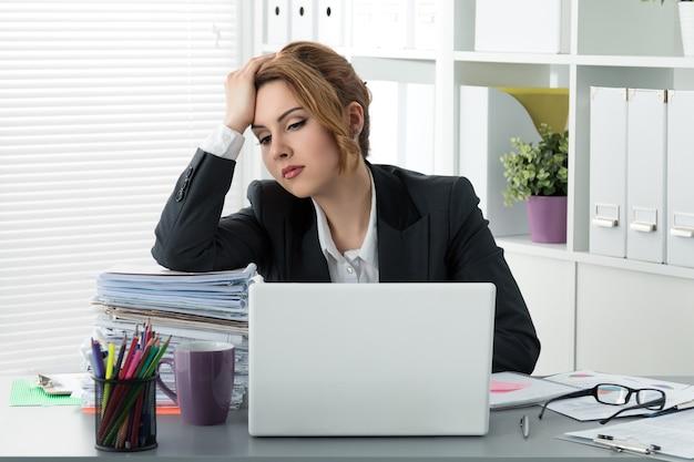 Femme d'affaires stressé fatigué assis avec une énorme pile de papiers