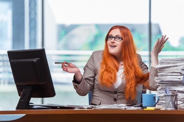 Femme d'affaires stressée avec une pile de papiers