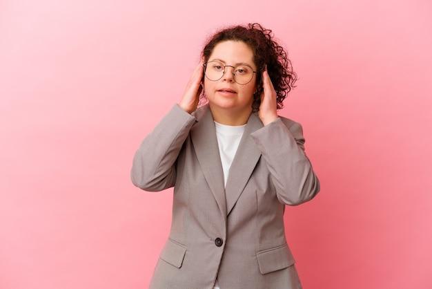 Femme d'affaires avec le syndrome de down isolé sur un mur rose couvrant les oreilles avec les mains