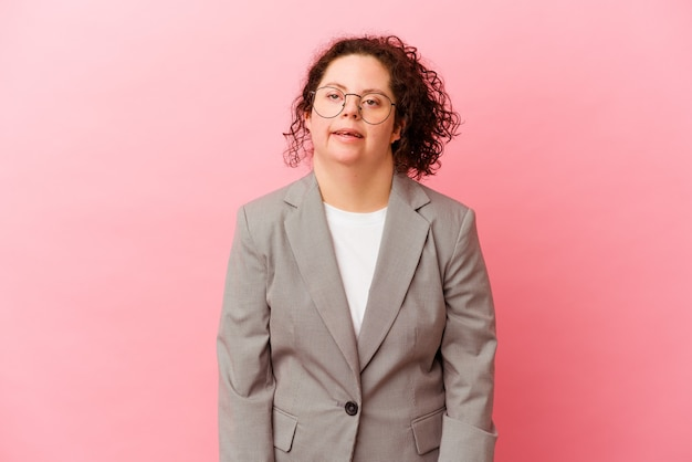 Femme d'affaires avec le syndrome de down isolé sur un mur rose heureux, souriant et joyeux