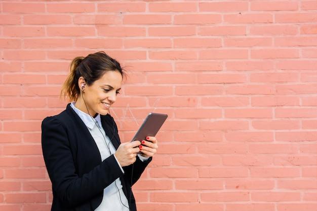 Femme d'affaires avec une tablette et un casque dans un fond de mur de briques rose clair avec espace copie