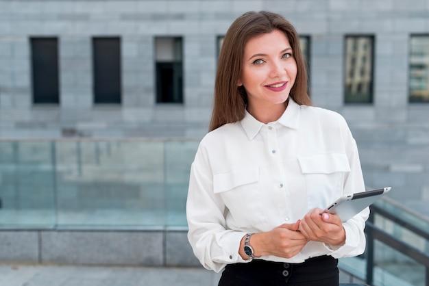 Femme d'affaires avec une tablette dans la rue