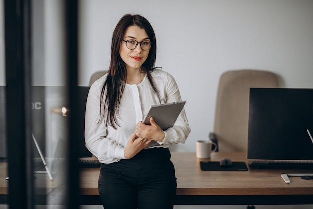 Femme d'affaires avec tablette debout au bureau