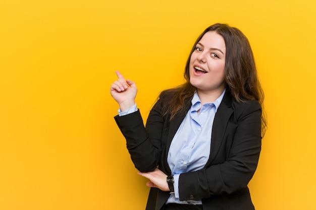 Femme d'affaires de taille plus jeune caucasien souriant gaiement pointant avec l'index.
