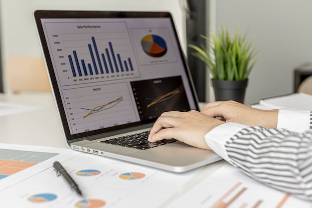 Une femme d'affaires tapant sur un clavier d'ordinateur portable, elle prépare un résumé financier à apporter à une réunion avec des partenaires commerciaux. concept de gestion financière de l'entreprise. vérification des informations financières.
