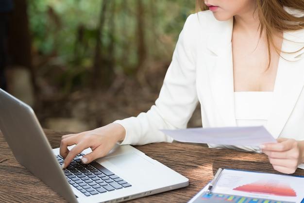 Femme d'affaires en tapant le document sur un ordinateur portable.