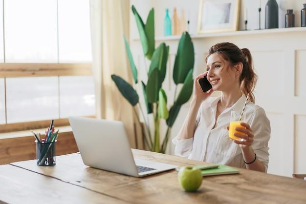 Femme d'affaires tapant un e-mail sur un ordinateur portable au bureau à domicile