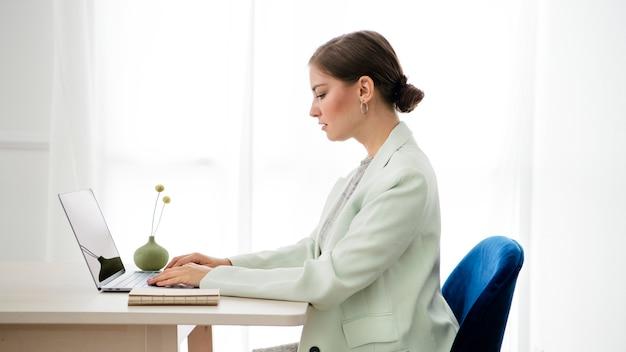 Femme d'affaires tapant sur son ordinateur portable sur une table en bois