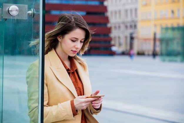 Femme d'affaires taper un message par téléphone sur la place de la ville