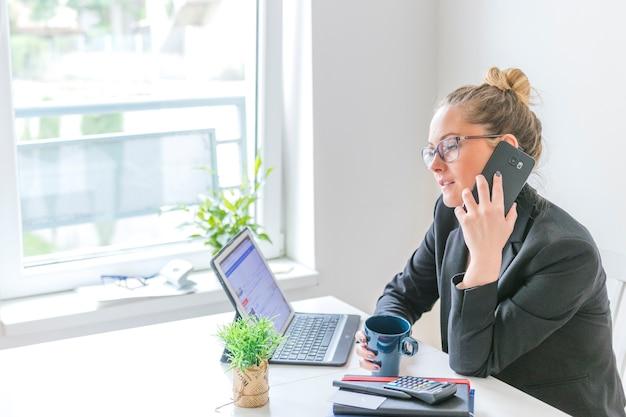Femme affaires, à, tasse café, conversation téléphone portable, dans bureau
