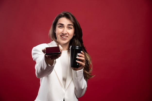 Femme d'affaires avec une tasse de café offrant un téléphone