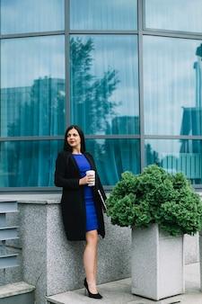 Femme d'affaires avec une tasse de disposition et café devant le bâtiment en verre