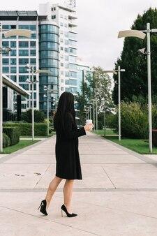 Femme d'affaires avec une tasse de disposition marchant sur le trottoir devant le bâtiment