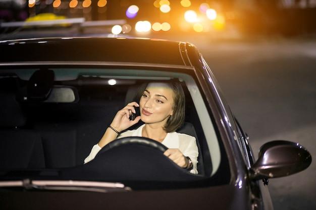 Femme d'affaires avec le téléphone dans la voiture