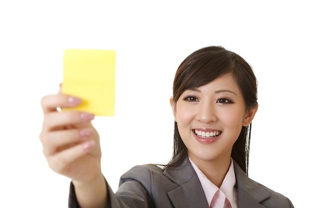 Femme d'affaires tenant un bâton de mémo jaune, portrait agrandi sur blanc.