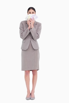 Femme d'affaires tenant des billets ventilés devant le visage