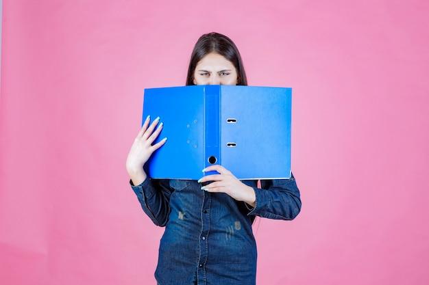 Femme d'affaires tenant un dossier de projet ouvert et cachant son visage derrière elle