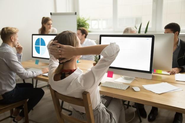 Femme affaires, tenant mains, derrière, tête, reposer, finition, vue postérieure