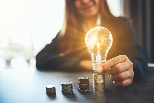 Femme d'affaires tenant et mettant l'ampoule sur la pile de pièces sur la table pour économiser de l'énergie et de l'argent concept