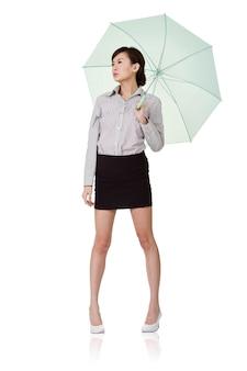 Femme d'affaires tenant un parapluie de vert, isolé sur un mur blanc.