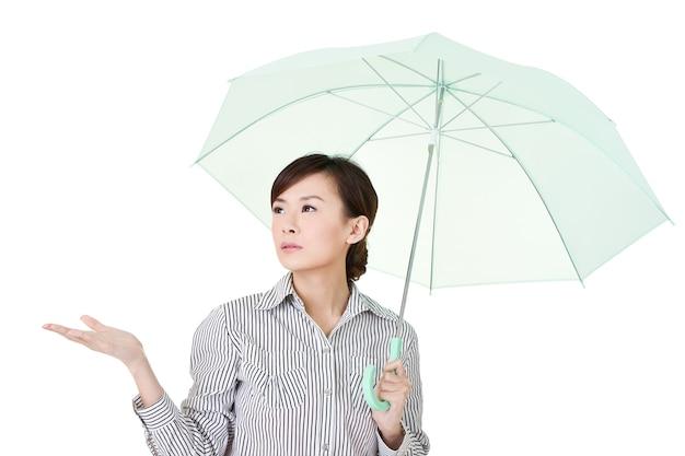 Femme d'affaires tenant un parapluie de vert, portrait agrandi sur un mur blanc.